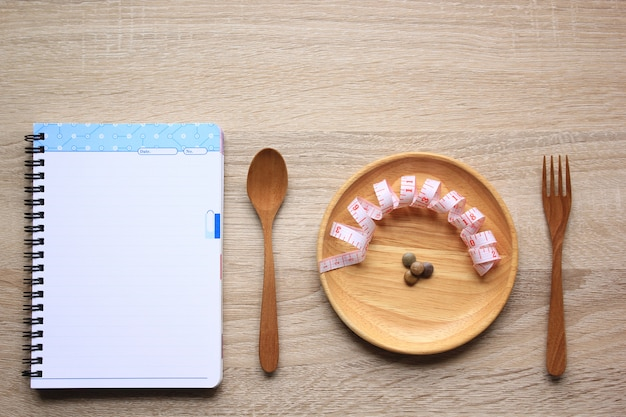 Pellet di verdure e nastro di misura nella ciotola di legno con cucchiaio e forchetta pagina di quaderno legno e vuoto