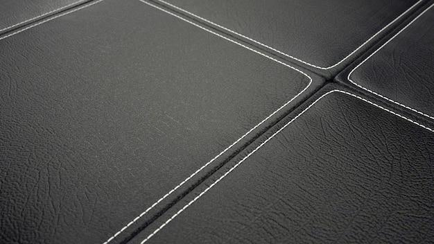 Pelletteria, dettaglio di piastrelle in pelle nera cucita.