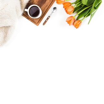 Pelliccia; cucchiaio; tazza di caffè e un mazzo di tulipani arancione su sfondo bianco