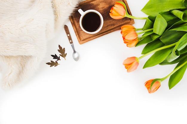 Pelliccia; cucchiaio; tazza di caffè e un tulipani arancioni su sfondo bianco