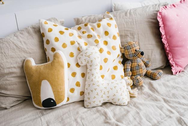 Peluche o cuscino a forma di un unicorno, orso e cuscini sul letto