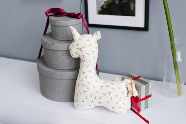 Peluche unicorno per bambini e tre scatole regalo rotonde legate con nastro bordeaux
