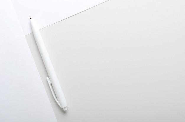 Penna bianca su carta grigia e bianca sulla scrivania