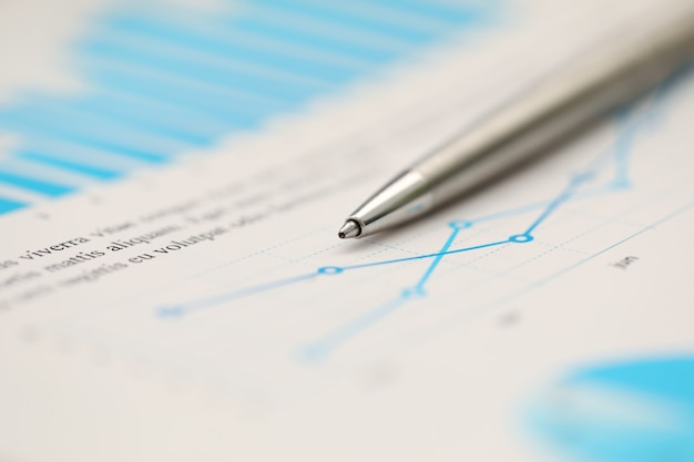 Penna d'argento che si riposa al documento statistico importante alla tavola di lavoro vuota