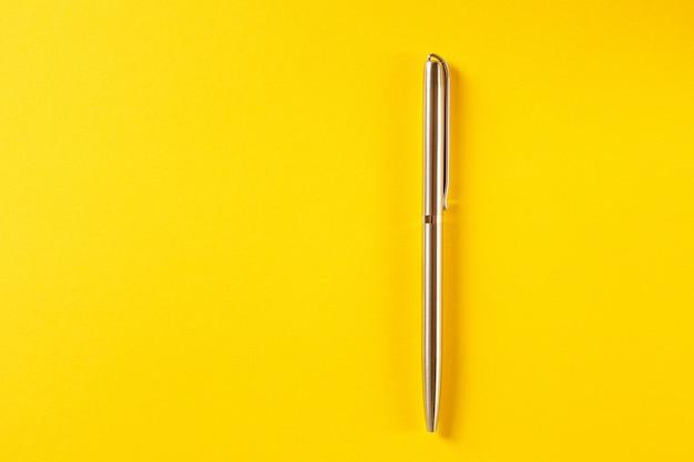 Penna del metallo isolata su giallo