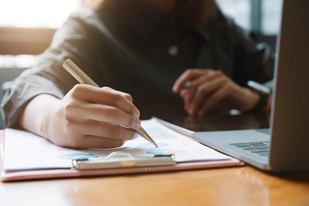 Penna dell'uomo d'affari che indica fatturato con report grafico grafico e utilizzare il computer portatile per i dati di analisi.