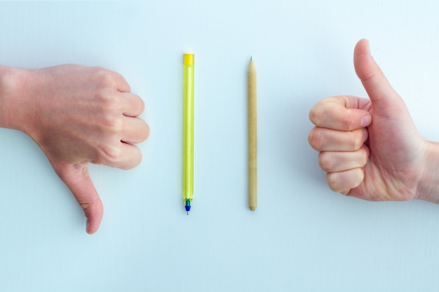 Penna di plastica e artigianale su una superficie blu. rifiuto della plastica e scelta di prodotti eco-compatibili. concetto di eco. protezione dell'ambiente e cura dell'ecologia