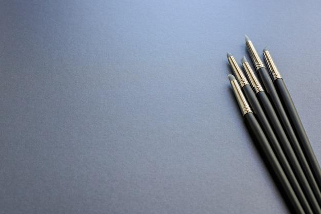 Penna di punta del silicone di fornitura di arte isolata su priorità bassa grigio scuro.