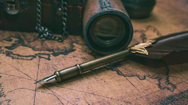 Penna di spoletta della piuma bronzea antica sulla mappa di vecchio mondo