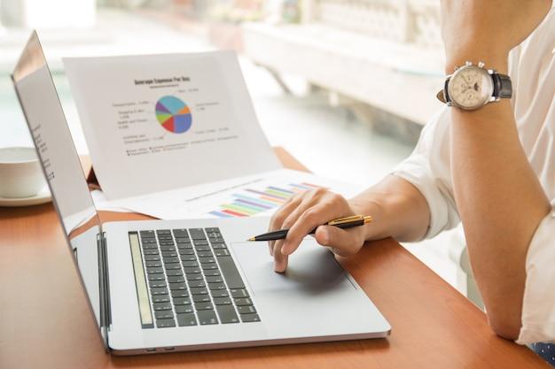 Penna di tenuta dell'uomo d'affari che lavora al computer portatile con il rapporto finanziario del grafico sulla tavola.