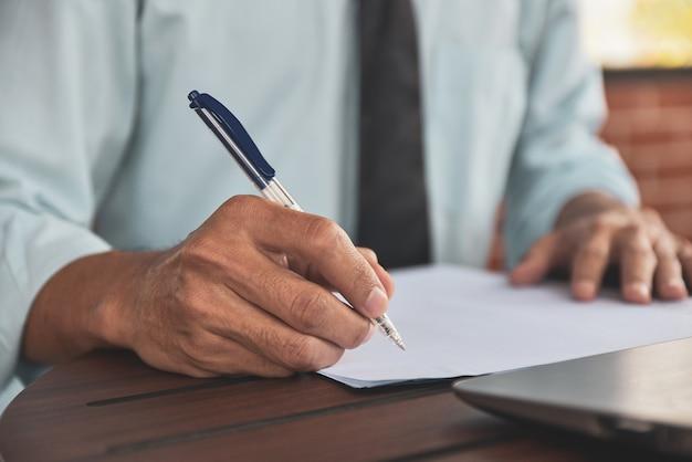 Penna di tenuta dell'uomo d'affari e scrivere sulle carte
