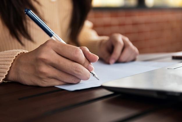 Penna di tenuta della donna di affari e scrivere sui documenti