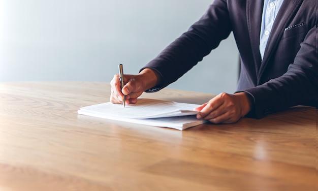 Penna di uso del vestito nero di usura dell'uomo di affari alla firma dei documenti del contratto su uno scrittorio di legno nell'ufficio
