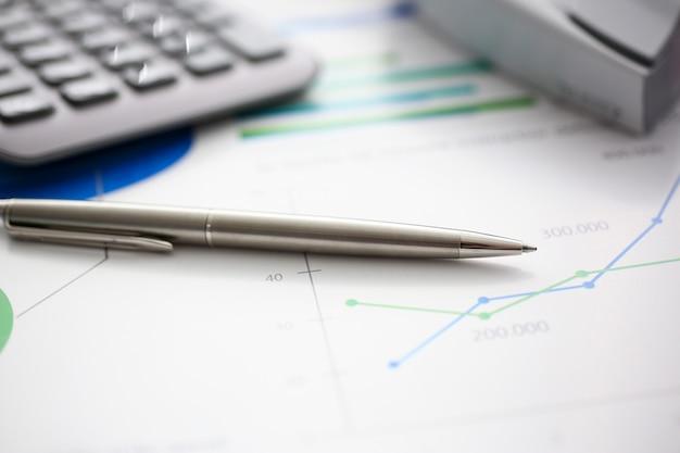 Penna e calcolatore d'argento nel luogo di lavoro pronti per essere utilizzati