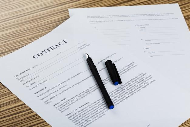 Penna e documenti del contratto sullo scrittorio di legno