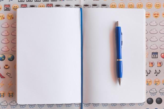 Penna e quaderno su sfondo emoji