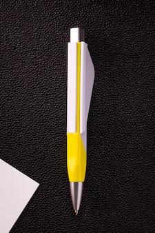 Penna ellow e carta bianca su sfondo scuro.