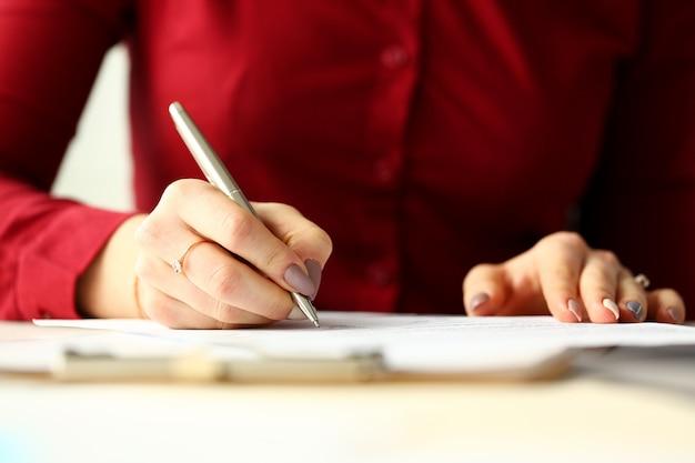 Penna femminile dell'argento della tenuta di impiegato che compila un certo modulo di domanda