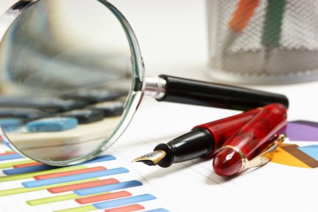 Penna, lente d'ingrandimento e il documento di lavoro con un diagramma