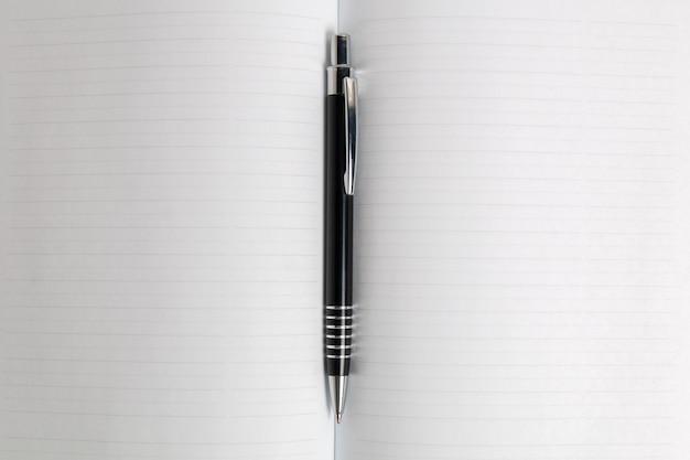 Penna nera in uno sfondo di diffusione pagina notebook