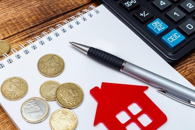 Penna rossa del blocco note della casa domestica sulle banconote e sulle monete