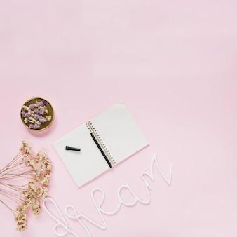 Penna sul blocco note a spirale con fiori e sogno testo su sfondo rosa