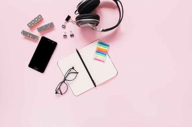 Penna sul diario vuoto; occhiali; e cancelleria con il cellulare su sfondo rosa
