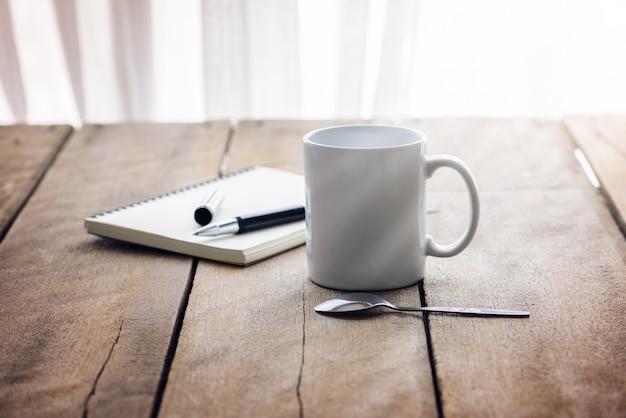 Penna sul taccuino con la tazza di caffè su di legno