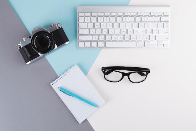 Penna vicino a notebook, fotocamera, occhiali e tastiera