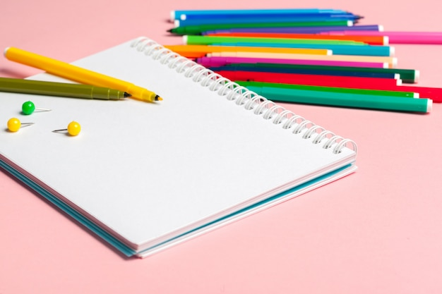 Pennarelli colorati con carta di blocco note vuota su sfondo rosa pastello