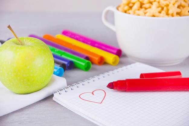 Pennarelli colorati, quaderno con scetch, ciotola di cereali a forma di stella e mela sullo sfondo grigio