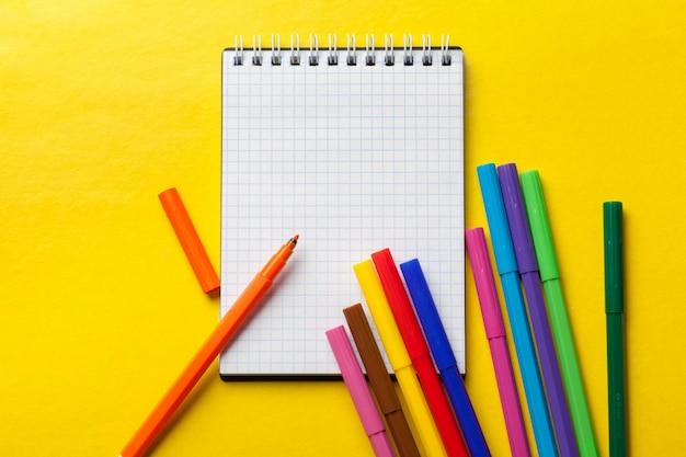 Pennarelli e blocco note bianco su giallo brillante