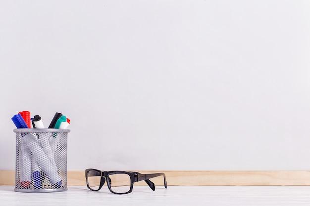 Pennarelli, occhiali e una lavagna bianca.
