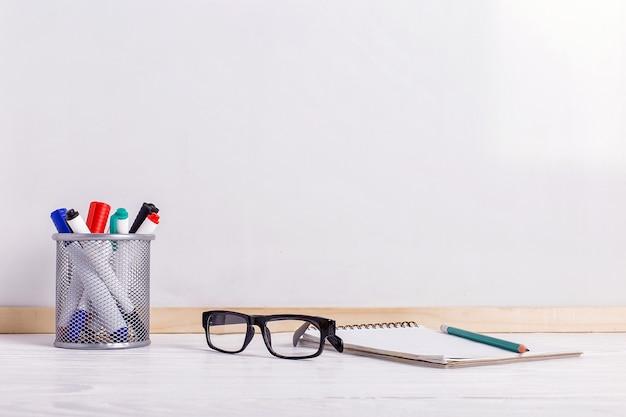 Pennarelli, occhiali, quaderno, matita e lavagna bianca.