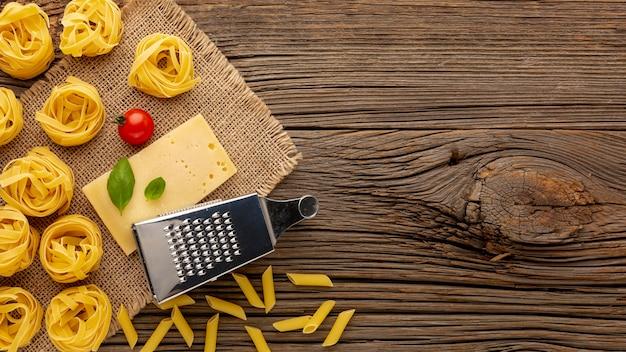 Penne e tagliatelle crude con formaggio a pasta dura e copia spazio