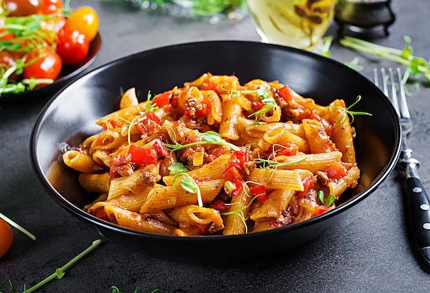Penne in salsa di pomodoro con carne, pomodori decorati con germogli di pisello su un tavolo scuro