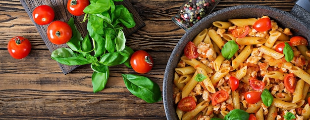 Penne in salsa di pomodoro con pollo, pomodori, decorato con basilico su un tavolo di legno. cibo italiano. pasta al ragù. vista dall'alto. disteso
