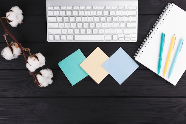 Penne vicino a notebook, ramoscello, documenti e tastiera