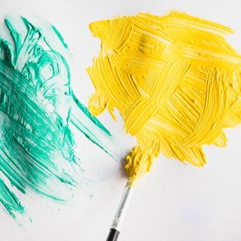 Pennellata di vernice verde e gialla sul foglio di carta bianca