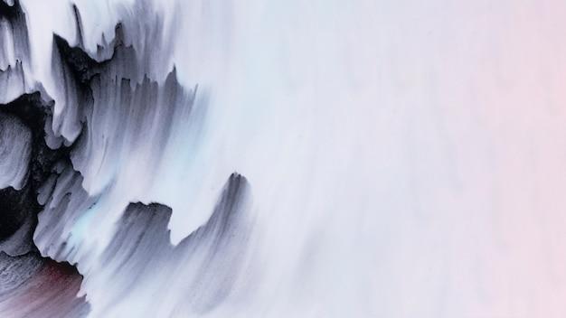 Pennellate di colore nero sull'angolo della superficie bianca ruvida