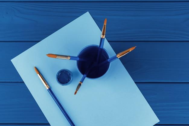 Pennelli blu su colore blu classico, vista da sopra