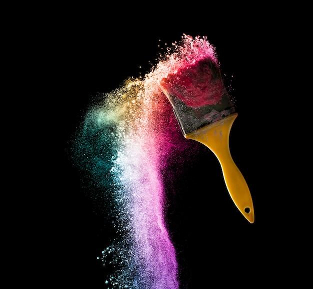 Pennelli con esplosione di colore polvere astratta isolato su sfondo nero