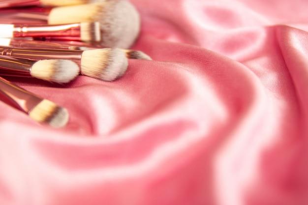 Pennelli cosmetici trucco professionale su sfondo di tessuto ondulato rosa seta stropicciata.