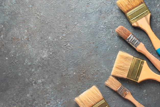 Pennelli degli strumenti di disegno sul fondo grigio del cemento, vista superiore