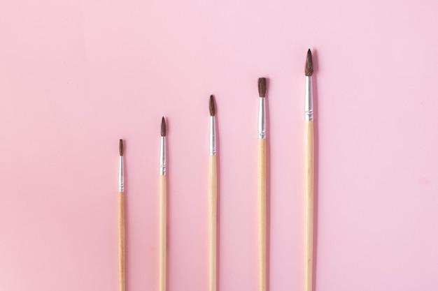 Pennelli isolati su carta rosa, copia spazio
