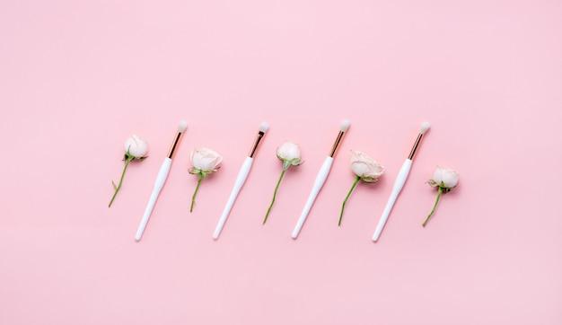 Pennelli per il trucco e fiori su sfondo bianco. copyspace vista orizzontale.