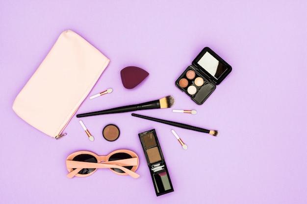 Pennelli per il trucco; tavolozza ombretto e occhiali da sole su sfondo viola