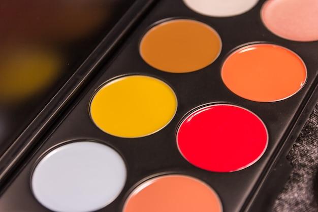 Pennelli per trucco e palette di ombretti nei toni del beige e dell'arancio, close-up cosmetici