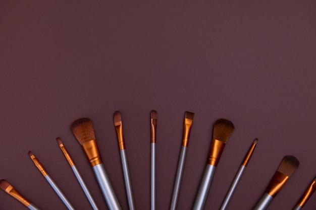 Pennelli trucco cosmetico su uno sfondo marrone copia spazio concetto di bellezza cosmetica