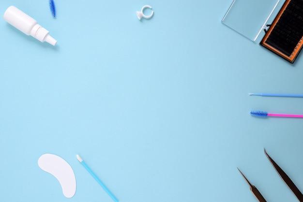 Pennelli trucco e cosmetici su sfondo blu. vista dall'alto, distesi, copia spazio